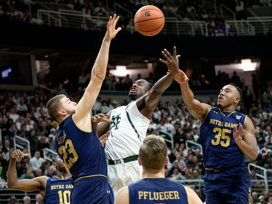 Michigan State's Joshua Langford, center, is fouled