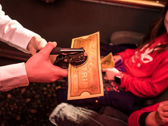 A conductor punches a ticket at the Polar Express event at the Whippany Train Museum.