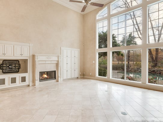 The family room has wall-to-wall windows overlooking