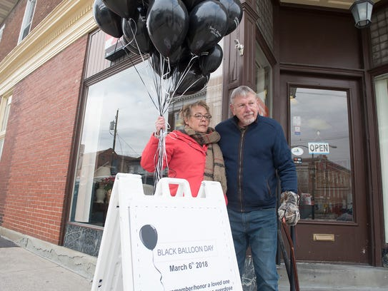 Carrol Rhodes and his wife, Vicki, pose in front of a Black Balloon Day sign. They placed black balloons around the Greencastle square on Tuesday, March 6, 2018, to raise awarenesss for drug addiction and overdose. The Rhodes' daughter, Teri, died from a drug overdose.