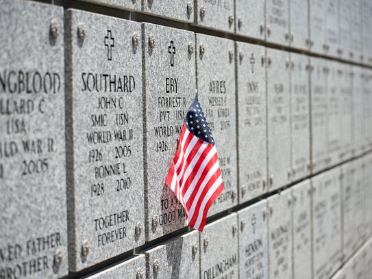 A flag is pinned to a memorial wall at the Northern