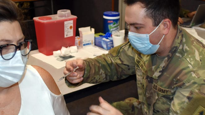 An Army National Guard medic administers a dose of the Pfizer vaccine in Coldwater.