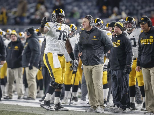 Iowa junior center James Daniels discusses with offensive coordinator Brian Ferentz on the sideline against Boston College during the 2017 Pinstripe Bowl at Yankee Stadium in Bronx, New York on Wednesday, Dec. 27, 2017.
