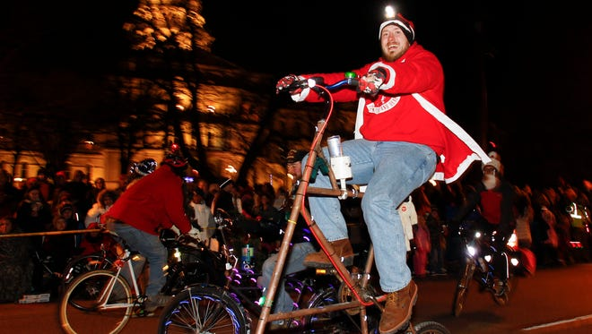 Dane Reynolds from Jasper, Indiana rides the tallest bike as a visiting  member of the Lansing Bike Party's entourage Friday, November 20, 2015, during the 31st annual Silver Bells in the City.