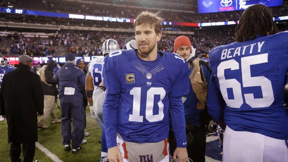 New York Giants quarterback Eli Manning (10) leaves the field after an NFL football game against the Dallas Cowboys, Sunday, Nov. 24, 2013, in East Rutherford, N.J. The Cowboys won 24-21.