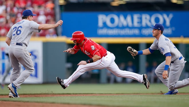 Cincinnati Reds second baseman Jose Peraza (9) is caught and tagged out by Los Angeles Dodgers first baseman Cody Bellinger (35) in a run down after hesitating to steal second base in the bottom of the second inning at Great American Ball Park on Friday, June 16, 2017.