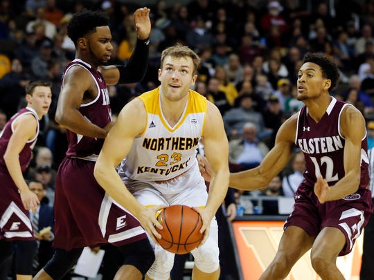 Northern Kentucky Norse forward Carson Williams (23) pushes his way through the defense of Eastern Kentucky Colonels guard Dedric Boyd (20) and forward Zach Charles (12) in the first half at BB&T Arena Sunday December 10, 2017.