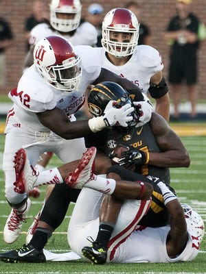 Missouri's Bud Sasser is wrapped up by Indiana's Michael Hunter, bottom, David Cooper, left, and Mark Murphy, top, during the fourth quarter of an NCAA college football game Saturday, Sept. 20, 2014, in Columbia, Mo. Indiana upset Missouri, 31-27. (AP Photo/L.G. Patterson)