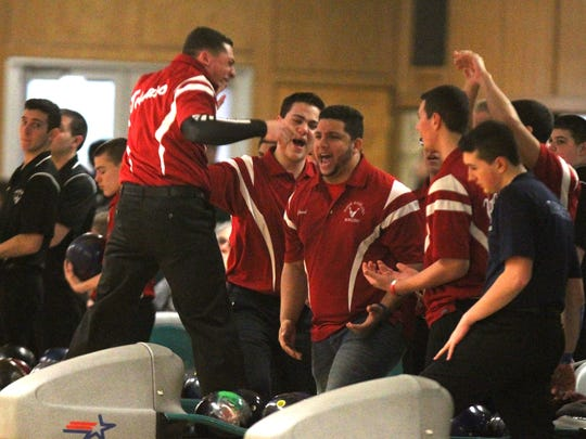 North Rockland's Johnny Toscano jumps in celebration after throwing a strike at the Section 1 boys bowling tournament while assistant coach Alex Rodriguez (middle) and teammates cheer on at Fishkill Bowl on Feb. 7, 2017.