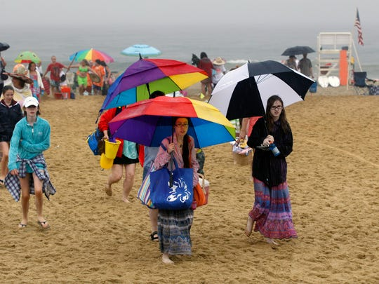 People pack up and leave the beach in the rain during