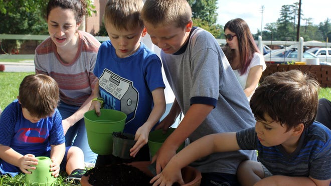 Olivia Medoff, a registered behavior technician at the St. Gerard House in Hendersonville, supervises a gardening activity with a group of youngsters who have been diagnosed with autism spectrum disorder. The photo was taken about three years ago.