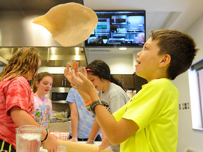 Noah Meyer, 9, tosses pizza dough in the air during Camp Fuel at Sanford Heart Hospital in Sioux Falls, S.D., Wednesday, June 11, 2014.