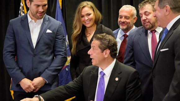 Gov. Andrew Cuomo, center, reaches for a pen as he signs into law a measure that will allow professional mixed martial arts in New York, Thursday, April 14, 2016. Behind him are UFC athletes Chris Weidman, left, and Ronda Rousey, and James Dolan, second from right, executive chairman of Madison Square Garden. New York was the last U.S. state to prohibit the bouts. (AP Photo/Mark Lennihan)