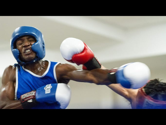 Stephen Miller, left, takes a punch from Martin Moreno at an amateur boxing event at the Florida National Guard Armory in Tallahassee, Fla on Saturday, July 26, 2014.