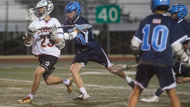 Rocky Mountain High School midfielder Matteo Vattano tries to get around Ralston Valley's defense  during a game Wednesday night at French Field. The Lobos won 15-4.