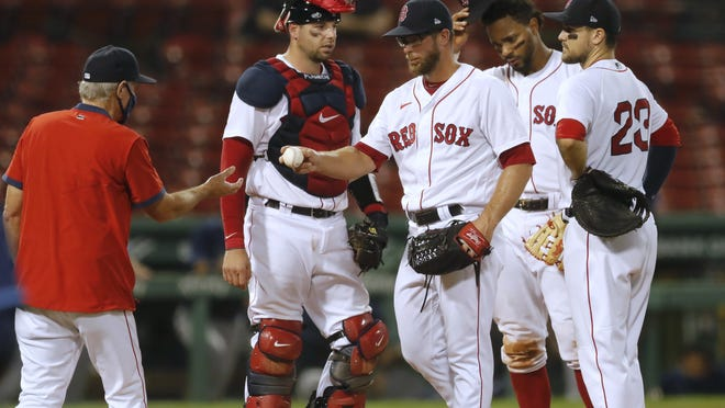 The Boston Red Sox's Marcus Walden, center, hands the ball to manager Ron Roenicke during a pitching change in the fifth inning of Monday's game against the Tampa Bay Rays in Boston.