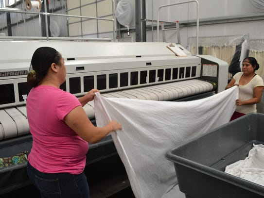 Workers prepare to feed sheets into the pressing machine