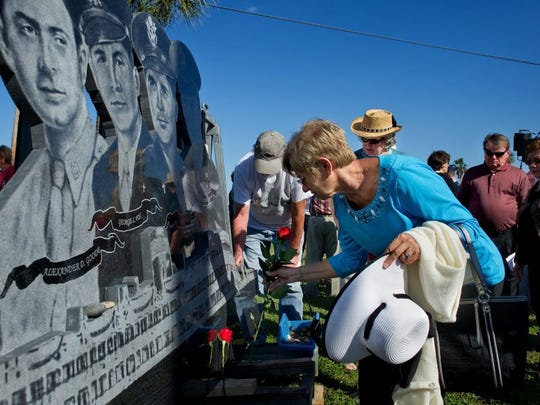 """Palma DeLuca, who is spending the winter in Fort Myers, places a rose on the newly unveiled monument dedicated to the """"Four Chaplains"""" at Riverview Park on Tuesday afternoon. Hundreds of residents attended the dedication of the monument that recognizes Alexander D. Goode, George L. Fox, Clark V. Poling and John P. Washington, who were killed on the U.S.A.T. Dorchester in 1943. (SAM WOLFE/SPECIAL TO TREASURE COAST NEWSPAPERS)"""