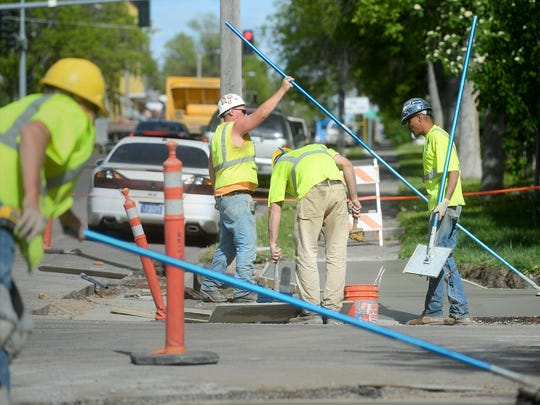 United Materials concrete finishers work on a project to add handicap ramps at sidewalk corners along 8th Street North on Tuesday afternoon.