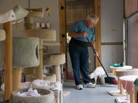 Volunteer Rudy Pecchia of Berkeley helps Jamie Sorrentino out in the Cat House at the Calling All Cats Sanctuary in Jackson.