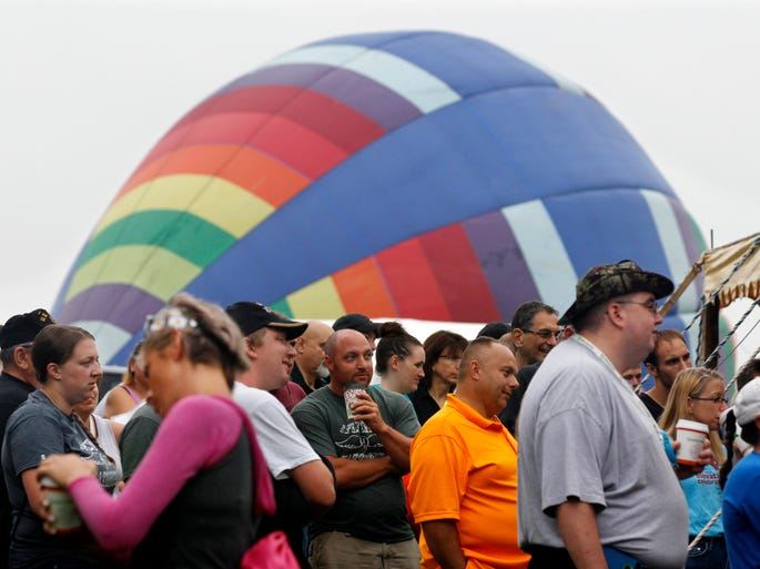 People gather as a hot air balloon inflates nearby at the 32nd annual OuickChek New Jersey Festival of Ballooning in Readington, N.J., on July 27, 2014.