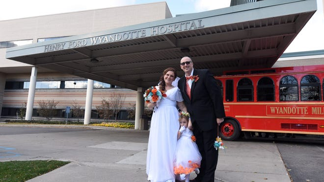 Paige Jarvis, 9, center, stands between her mother and the bride Crysta Danaher and groom William Anderson after their wedding at the Henry Ford Wyandotte Hospital on Saturday. The couple, shown in before photos (inset), met at the hospital.