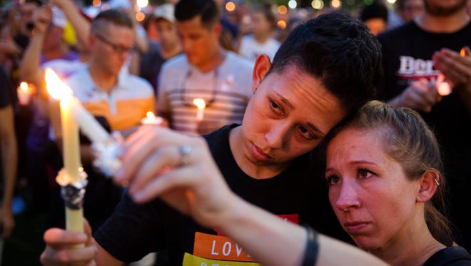 Jennifer, right, and Mary Ware light candles during a vigil for the victims of a mass shooting at the Pulse nightclub on Monday, June 13, 2016, in Orlando, Fla.