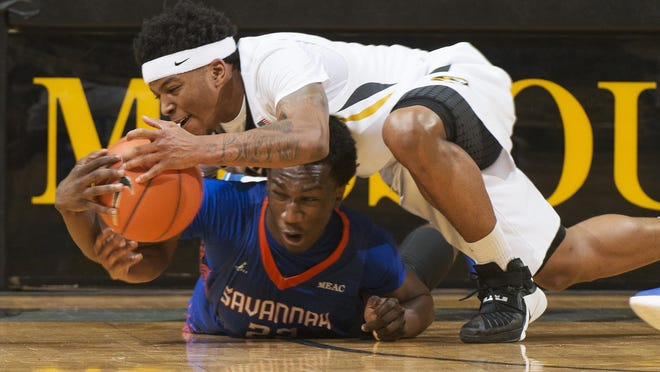 Missouri's Wes Clark, top, battles Savannah State's Dexter McClanahan for a loose ball during the first half Saturday in Columbia. Clark scored 22 points in Tigers' 81-50 win.