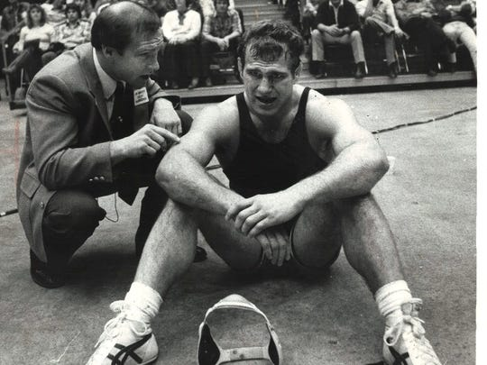 Iowa wrestling coach Dan Gable, left, talks to Ed Banach during a college match. Both men won Olympic gold medals.