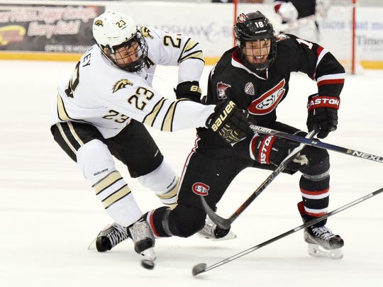 Western Michigan's Aaron Hadley (23) and St. Cloud State's Judd Peterson fight for a loose puck Jan. 23 at the Herb Brooks National Hockey Center.