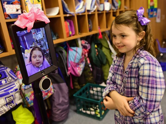 Reese Burdette, on the screen, visits with her sister,