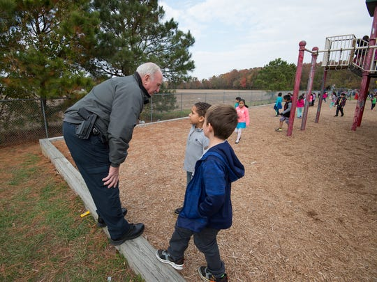 School safety monitor Ray Callaway talks with students on the playground at North Georgetown Elementary School in Georgetown.