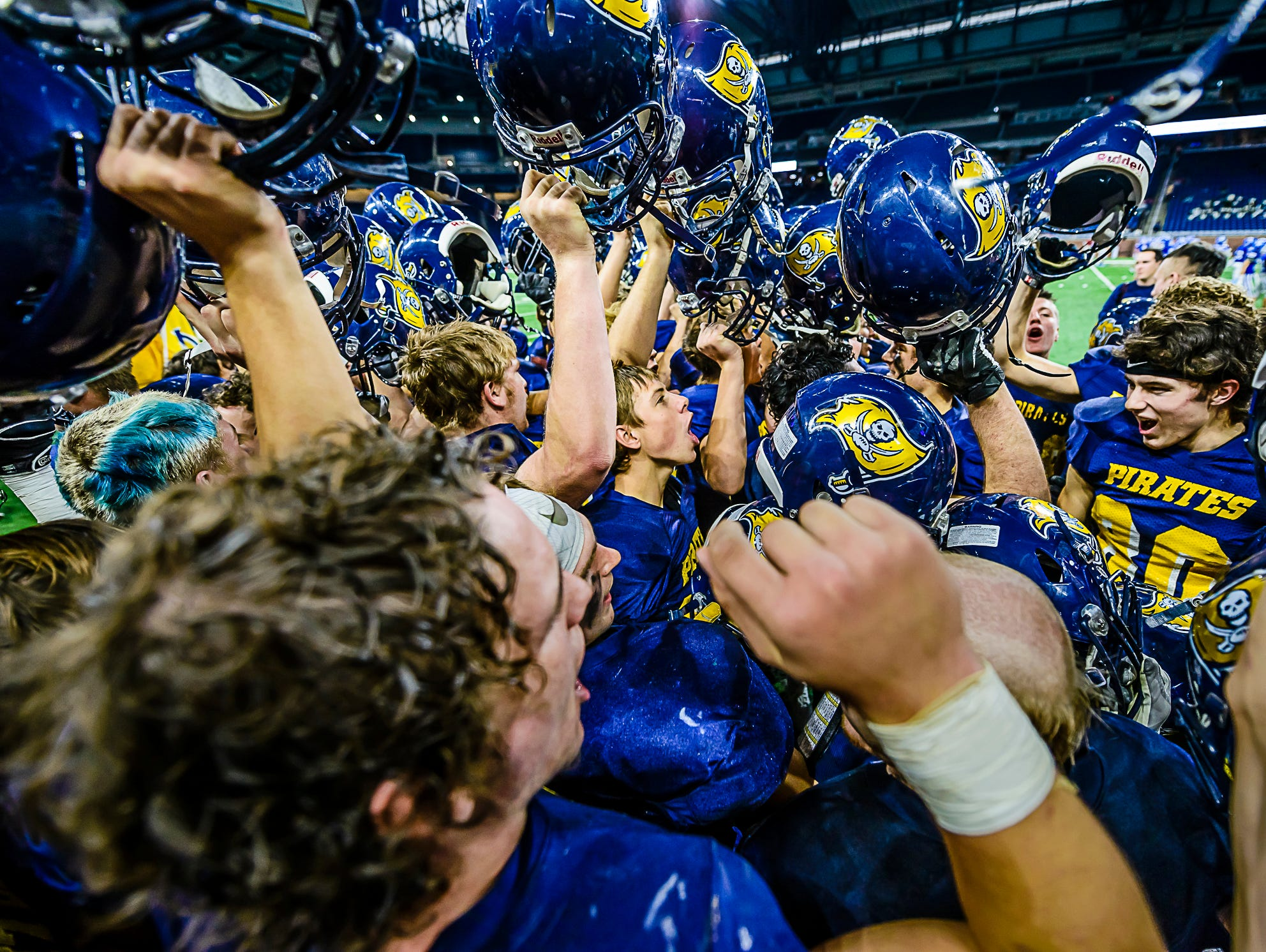 The Pewamo-Westphalia football team celebrates after their Division 7 state final win over Detroit Loyola Saturday November 26, 2016 at Ford Field in Detroit.