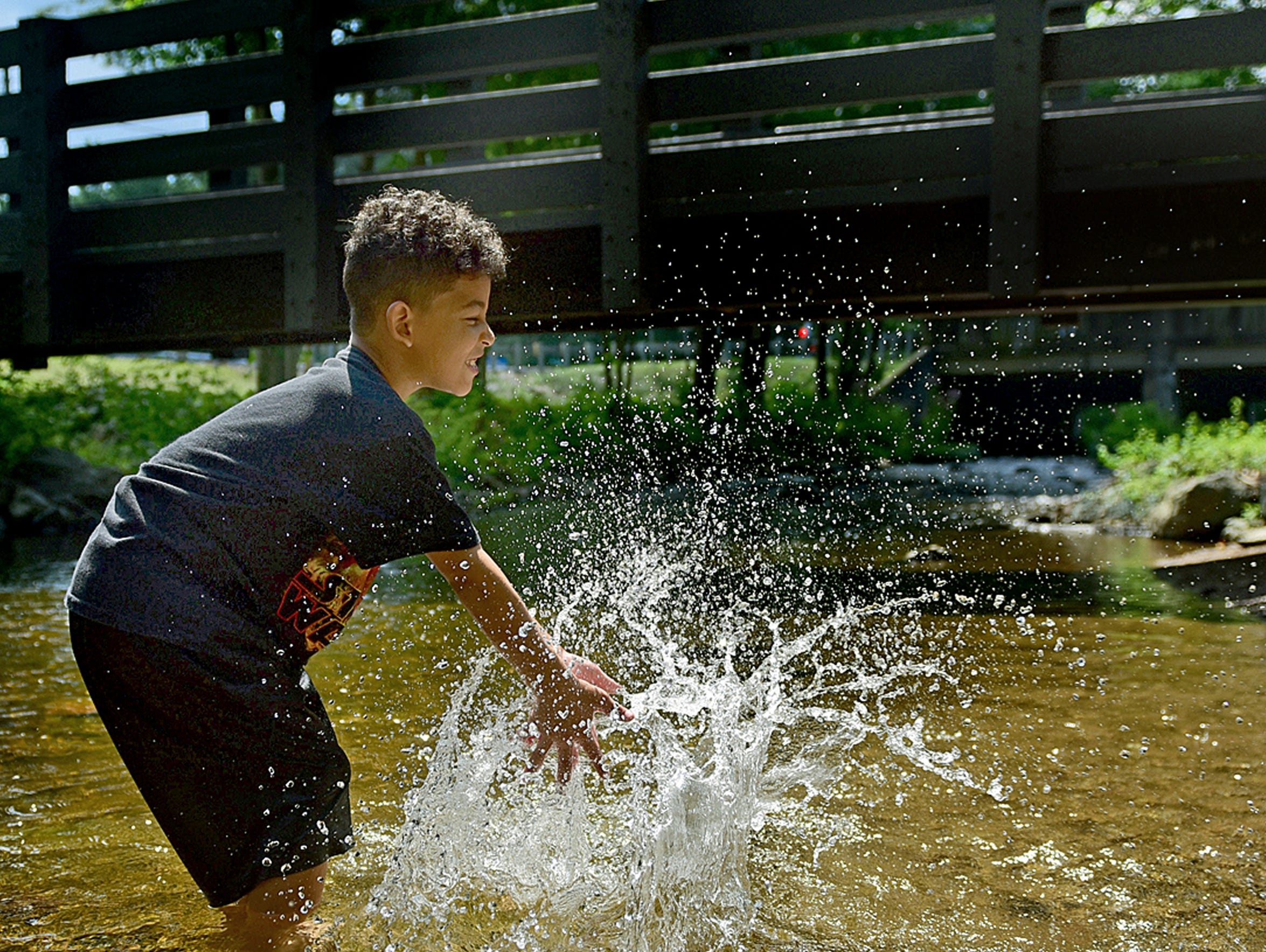 Christopher Wilkerson, 8, splashes water in a creek