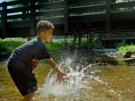 Christopher Wilkerson, 8, splashes water in a creek on Wednesday, August 2, 2017 at Caledonia State Park.