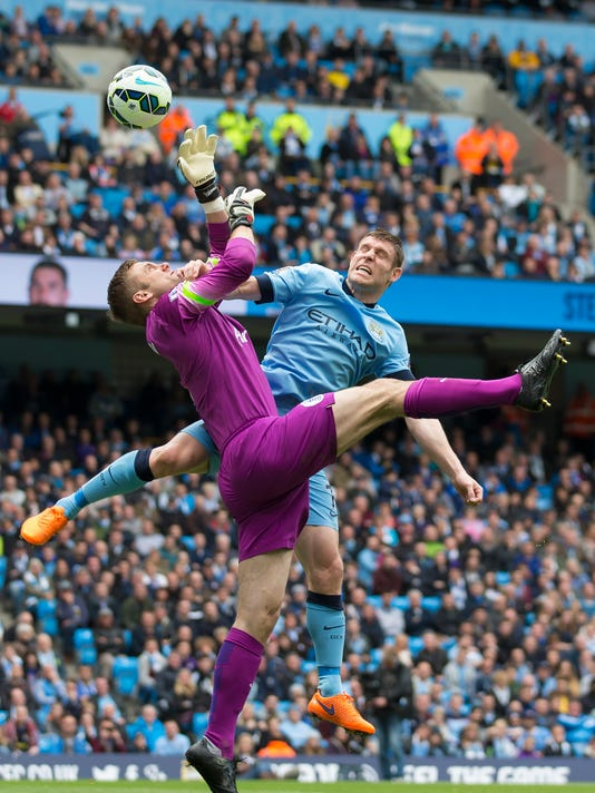 Manchester City's James Milner, right, fights for the ball against Queens Park Rangers' goalkeeper Robert Green during the English Premier League soccer match between Manchester City and Queens Park Rangers at the Etihad Stadium, Manchester, England, Sunday May 10, 2015. (AP Photo/Jon Super)