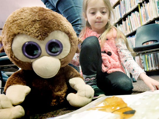 Ava Topper, 4, of Wrightsville, looks at a book with