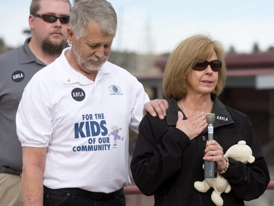 Carl Mueller and his wife, Marsha, speak during a playground