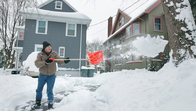 File photo: Paul Hogan of Penfield shovels his daughter's driveway last year on Harvard Street in Rochester.