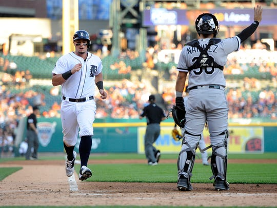 Tigers catcher James McCann (34) scores a run as White