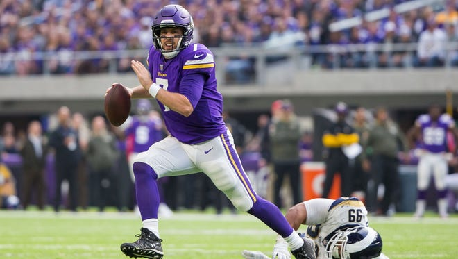 Minnesota Vikings quarterback Case Keenum (7) scrambles in the second quarter against the Los Angeles Rams defensive lineman Aaron Donald (99) at U.S. Bank Stadium.