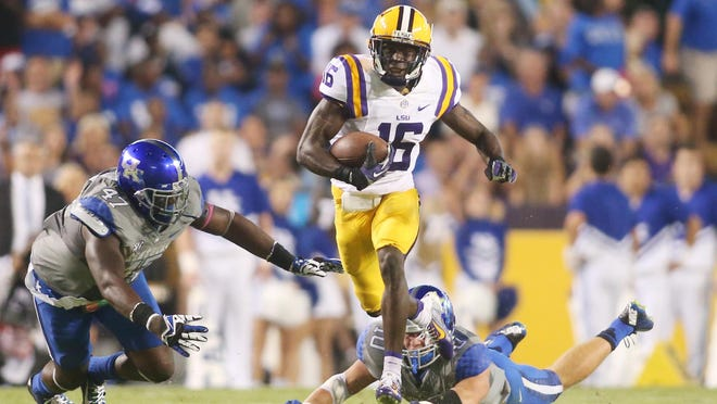 Oct 18, 2014; Baton Rouge, LA, USA; LSU Tigers defensive back Tre'Davious White (16) carries the ball past Kentucky Wildcats linebacker Tyler Brause (behind) and Kentucky Wildcats defensive end Jabari Johnson (47) on a return for a touchdown in the first quarter at Tiger Stadium. Mandatory Credit: Crystal LoGiudice-USA TODAY Sports