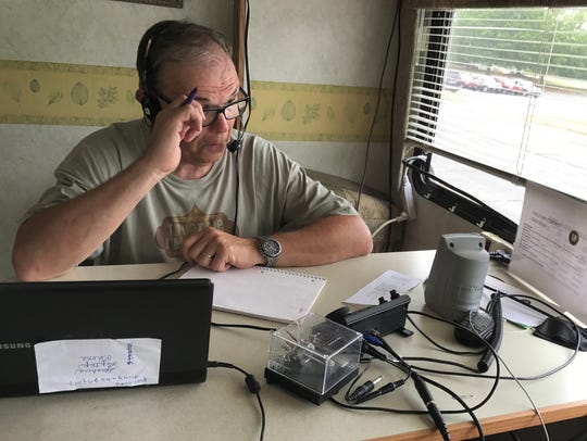 Russell Switzer operates a radio in a trailer in Anderson