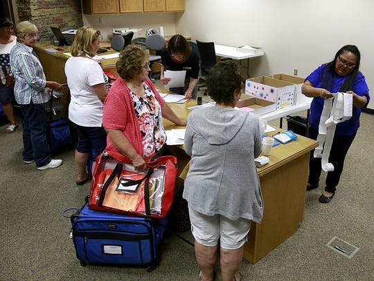 Election officials from the 34 voting centers in San Juan County arrive on Tuesday at the San Juan County Clerk's Office in Aztec.