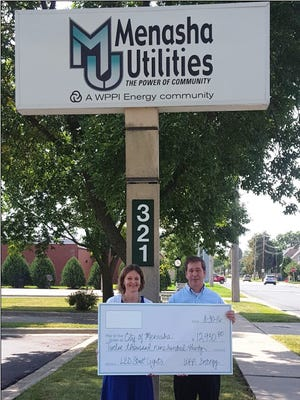Melanie Krause, general manager of Menasha Utilities, presents a check for $12,930 from WPPI Energy to Don Merkes, mayor of the city of Menasha.