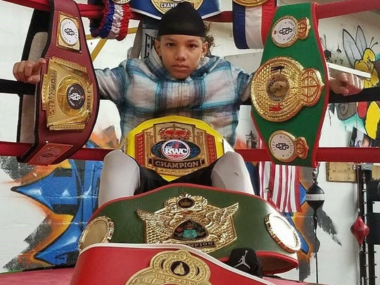 York teenager Antwoine Dorm Jr. is shown with some of boxing title belts.