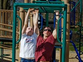 Father and daughter team up for a playground workout