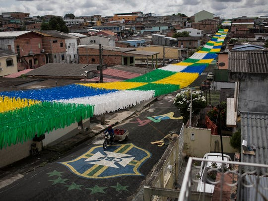 A man rides his motorbike under a canopy of ribbons through a street decorated in honor of the upcoming 2014 World Cup, in Manaus, Brazil on May 21, 2014.