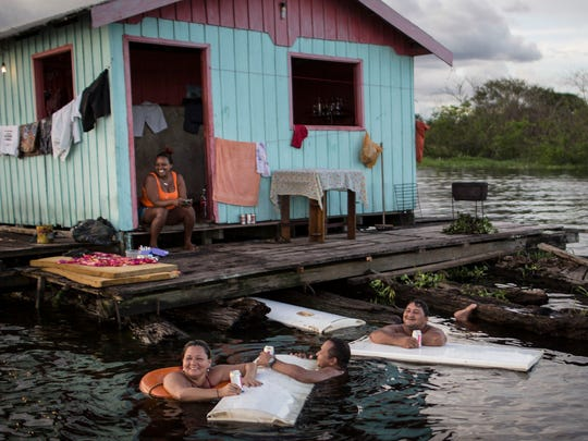 Residents use refrigerator doors as floating tables outside their floating house on the Rio Negro in Cacau Pirera, near Manaus, Brazil on May 18, 2014.