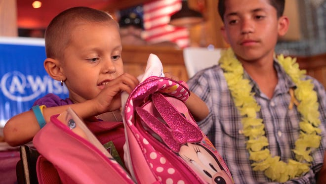 Desi Cechin, 6, sits beside her brother, Derek Cechin 14, while opening a gift from the Make-A-Wish Foundation in Palm Desert on Monday.